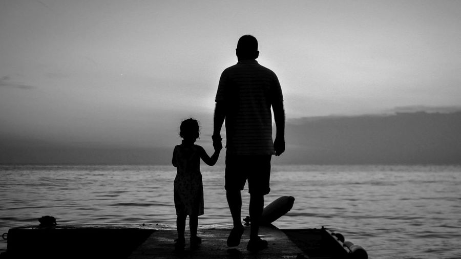 Rear View Of Silhouette Men With Daughter Standing On Pier Over Sea Against Sky