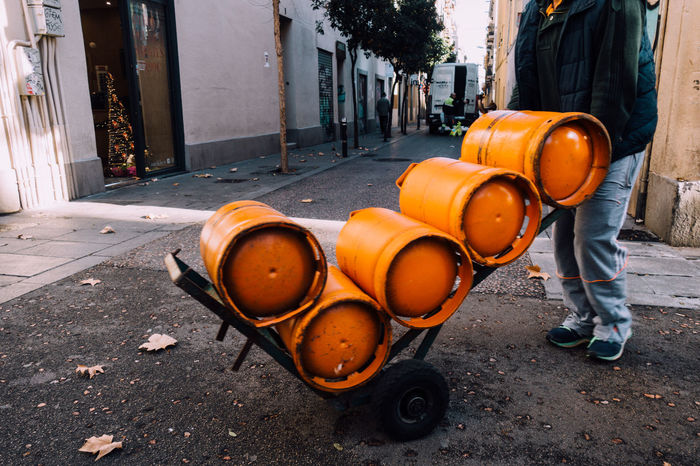 Delivery Delivery Service Gas Cylinder Working Working Hard Architecture Building Exterior Built Structure Carrier Day Delivery Boy Delivery Guy Drum Gas Bottles Gas Canister Men One Person Orange Color Outdoors People Real People Road Street
