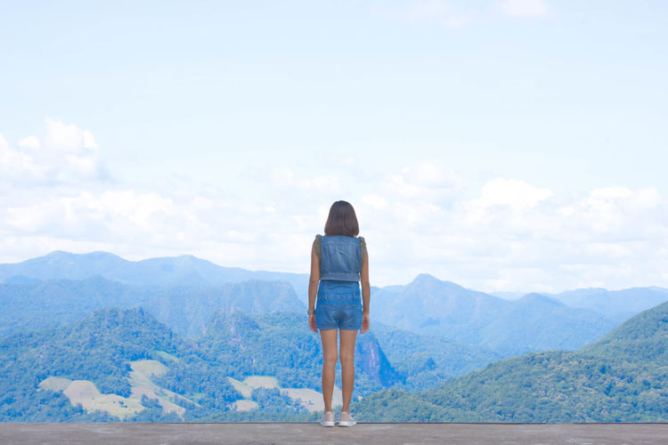 Rear view of woman standing against mountain and sky