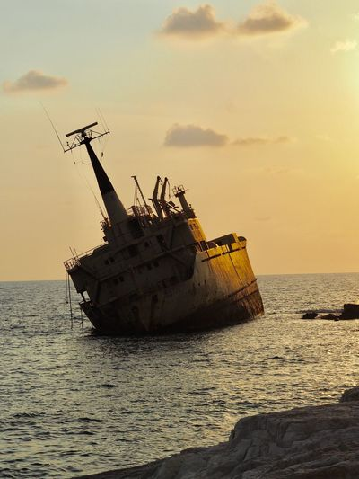 Damaged boat in sea against sky during sunset