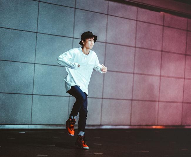 Full length of boy running in city