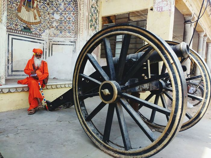 Full length of sadhu sitting by cannon