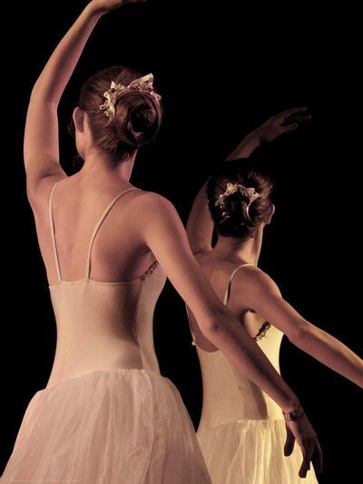 Female ballet dancers dancing against black background