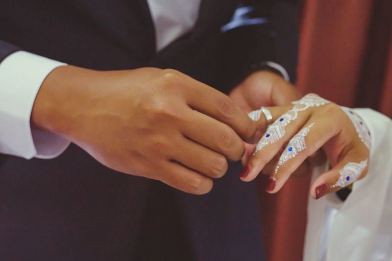 Midsection of bride and groom exchanging rings during wedding