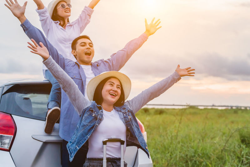 Happy young woman with arms raised against sky