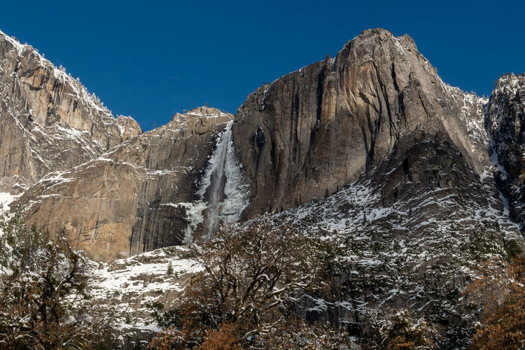 Yosemite Falls at Yosemite National Park in the winter of 2019 against a blue, cloudless sky Mountain Sky Scenics - Nature Rock Nature Winter Cold Temperature Snow Rock Formation Tranquility Rock - Object Non-urban Scene Day Tranquil Scene No People Formation Outdoors Mountain Peak Snowcapped Mountain Yosemite National Park National Park California USA Fall Waterfall
