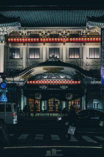 Illuminated street lights hanging on building