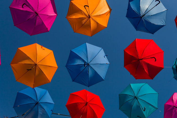 High angle view of umbrellas hanging against blue sky