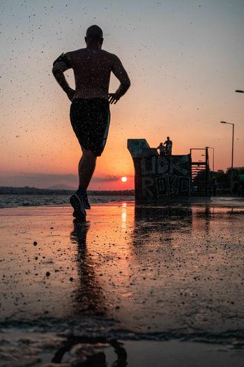 Full length of man on wet beach against sky during sunset