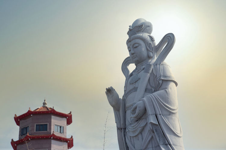 Scenic sky weather with chinese mythology deities statue in the foreground