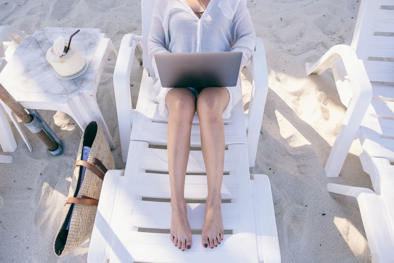 A woman using and typing on laptop computer with blank desktop screen while laying down on beach chair on the beach Space Sky Sitting Shoulder Sea Screen Sand Relax People Over Online  Notebook Nature Message Look Lifestyle Laying Laptop Internet Holiday Holding Hand Girl Female Empty Down Display Device Desktop Copyspace Copy Connection Computer Communication Coconut Chair Blue Beach Background