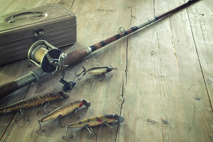 Antique fishing rod and lures on grunge wood surface Antique Bait Casting Cross Processed Equipment Fishing Grunge Hooks LINE Lures No People Old Reel Rod Surface Tackle Box Vintage Wood - Material