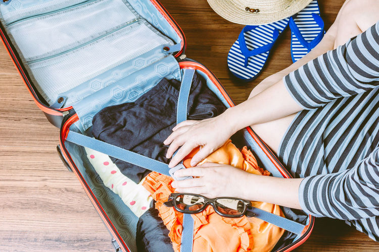 Woman packing a luggage on wooden floor Travel Adult Day Finger Hand High Angle View Holding Human Body Part Human Hand Indoors  Leisure Activity Lifestyles Luggage Men Midsection Packing Real People Table Technology Water Women
