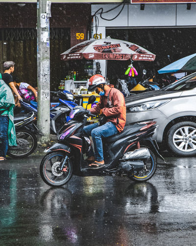 Man with umbrella on wet street during monsoon