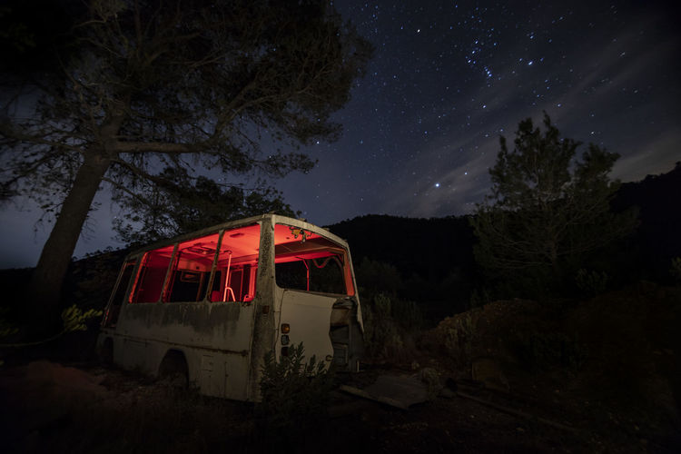 Red car on land against sky at night