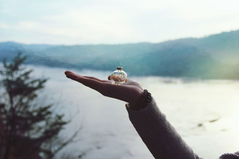 Close-Up Of Hand Holding Bauble Against Lake