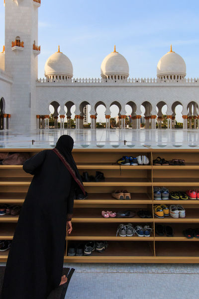 Abu Dhabi, United Arab Emirates - October 10,2014: Woman taking off her shoes before entering the Sheikh Zayed Grand Mosque Abu Dhabi Arabic Arch Architecture Building Exterior Built Structure City Life Dome Faith History Islam Outdoors People Sheik Zayed Mosque United Arab Emirates White Mosque