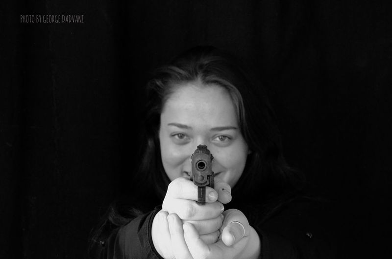 Portrait Of Smiling Woman Shooting With Handgun Against Black Background