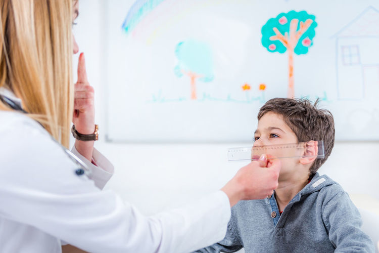 Pediatrician Examining Boy's Eyes with Ruler Doctor  Pediatrician Medical Child Boy School Boy Human Eye Ophtalmology Optometrist Pen Touch Light Checking Chekup Medicine Hospital Clinic Patient Health Kid Talking Stethoscope  Healthcare Care Childhood Female People Exam Professional Examination White Healthy Office Sick Adult Ilness Diagnostic Lifestyle Woman Examining Occupation Pediatric Specialist Examine Diagnosis Expertise Indoors  Pediatrist Visit Lab Coat