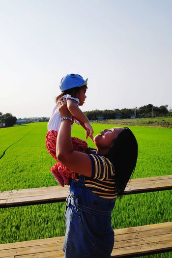 Side view of woman holding daughter with rice paddy in background against clear sky