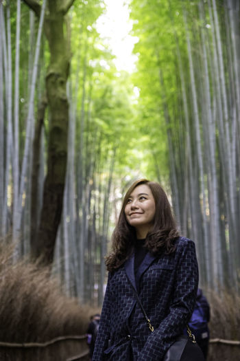 woman in bamboo forest, Japan Bamboo Forest Asian  Woman Tree Green Color Nature Portrait One Person Plant Young Adult Real People Smiling Looking At Camera Trunk Tree Trunk Long Hair Standing Women Hairstyle Day Outdoors WoodLand Beautiful Woman Warm Clothing