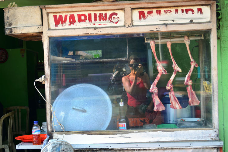 Reflection of woman on concession stand while photographing at street
