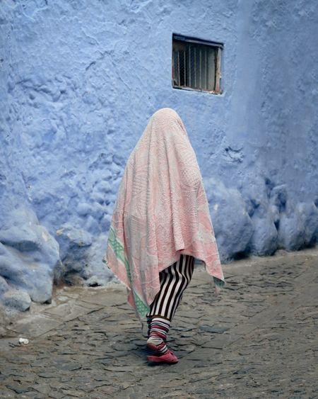 Rear view of woman covered by towel walking on footpath