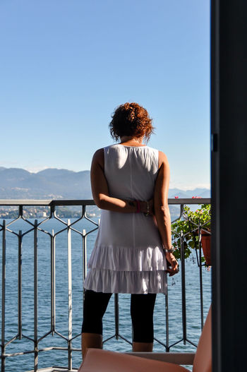 Rear View Of Young Woman Standing Against Lake Maggiore On Sunny Day