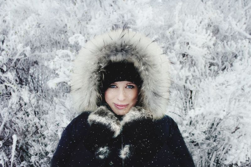 Portrait Of Smiling Young Woman Against Trees During Winter