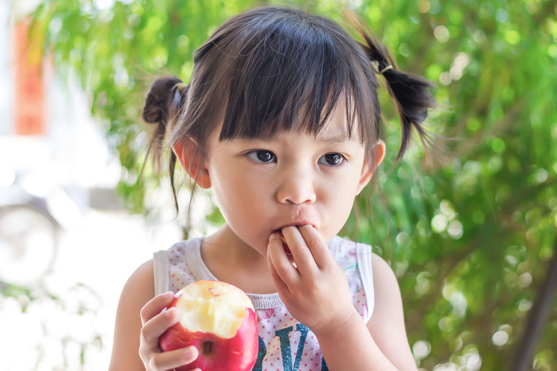 Cute girl eating apple outdoors