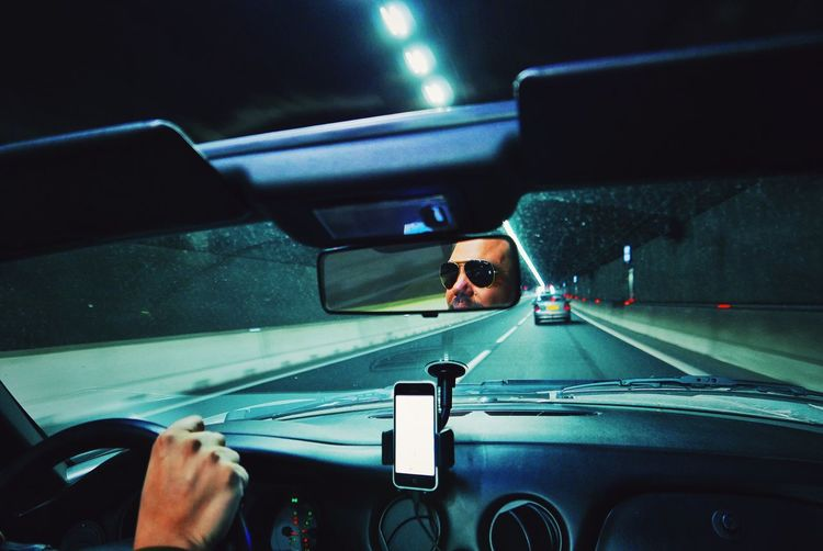 Reflection of man in rear-view mirror of car on road