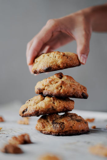 Cropped hand holding cookies over table