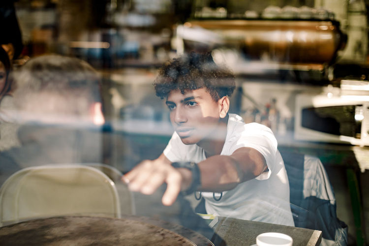 Portrait of young man looking away while sitting in restaurant