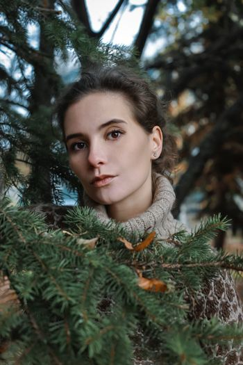 Portrait of young woman against trees