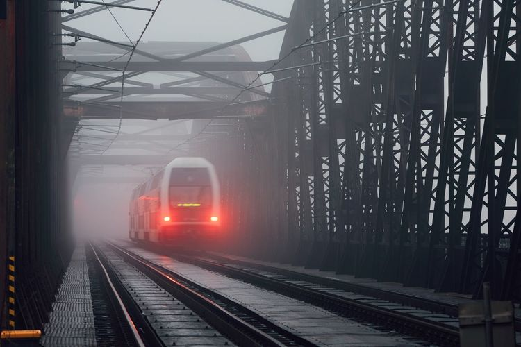 Train on railway bridge in foggy weather