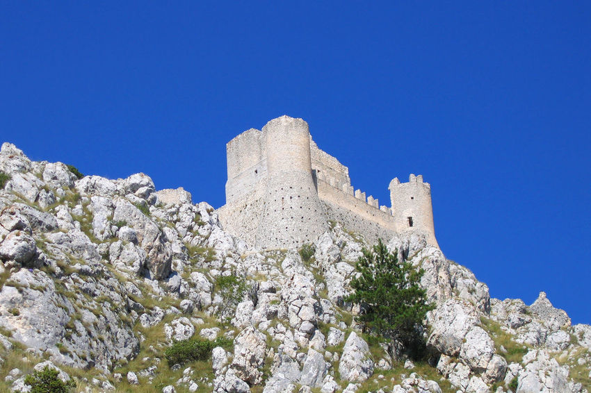 Abruzzo Rocca Di Calascio Architecture Beauty In Nature Blue Building Exterior Built Structure Calas Castle Clear Sky Copy Space Day Fort History Low Angle View Nature No People Outdoors Plant Sky Solid Sunlight The Past Tree