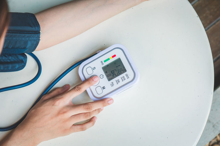 Midsection of woman checking blood pressure on table