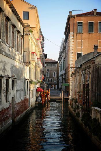 Canal amidst city against clear sky
