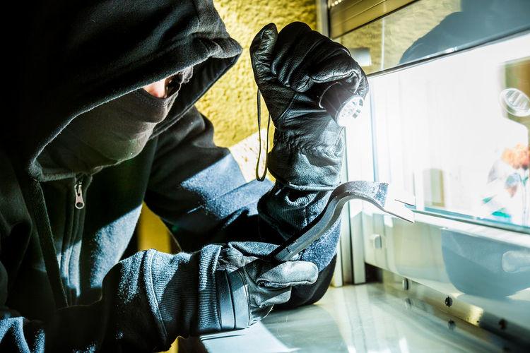 Burglar breaking glass window