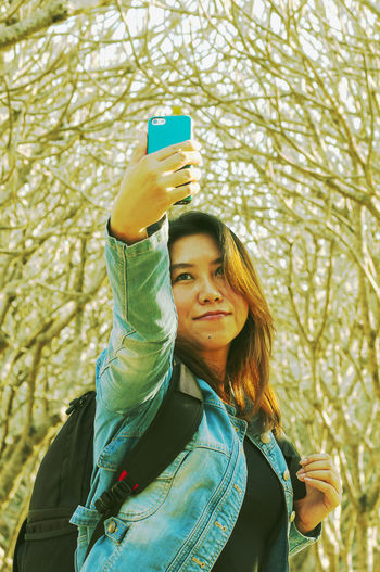 Woman taking selfie from phone while standing against trees