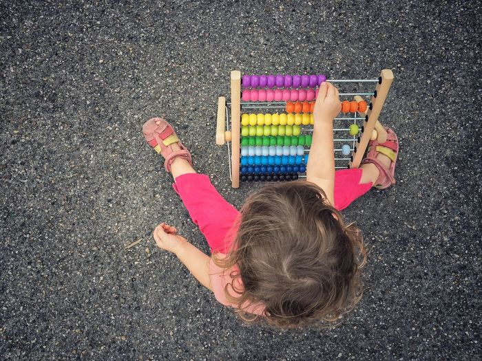 Directly above shot of young girl using colorful abacus