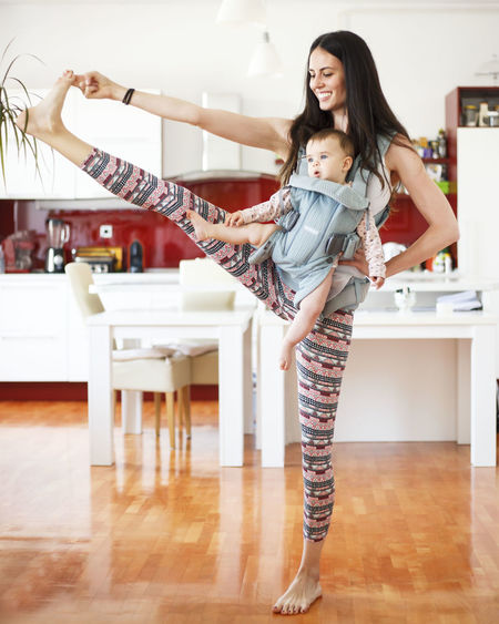 Mother With Toddler Daughter Exercising In Kitchen