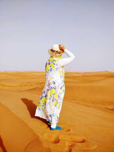 Full length of woman standing on sand against sky