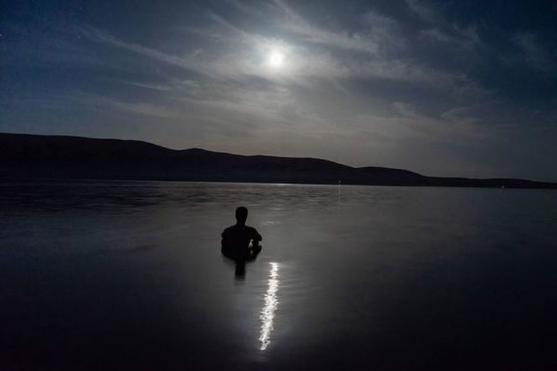 Silhouette man in lake against sky