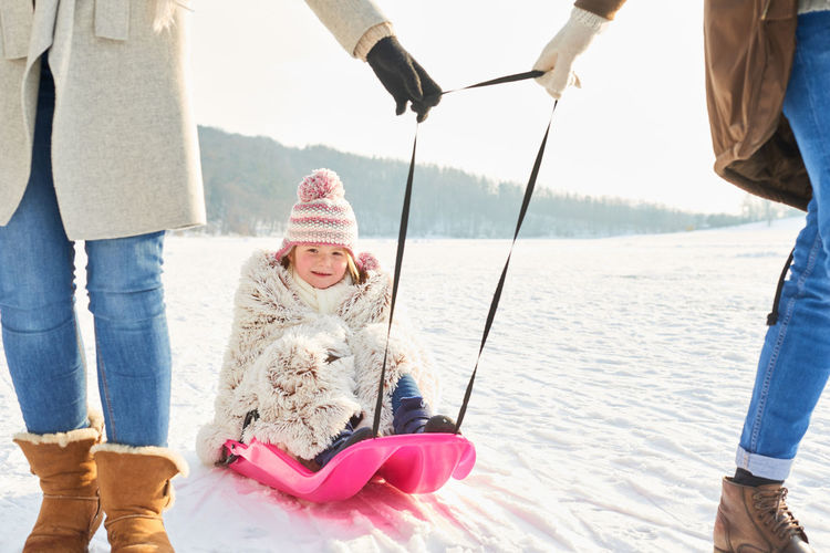 Low Section Of Parents Pulling Girl Sitting On Sled