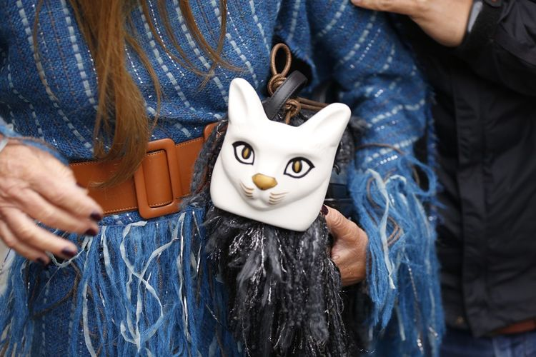 Midsection Of Woman Holding Purse With Cat Figurine