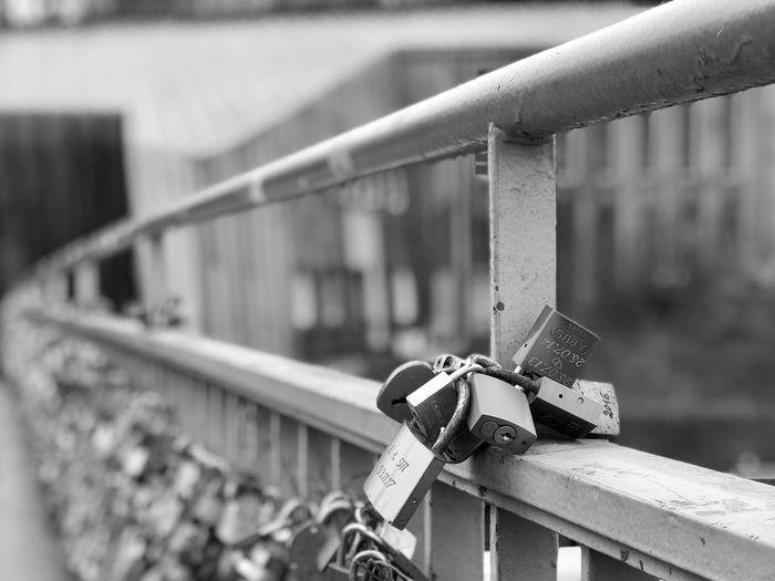 Close-up of padlocks on railing against bridge