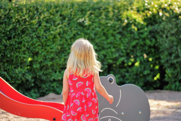 Rear view of girl standing by slide at playground