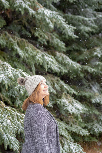 Woman wearing hat standing in forest