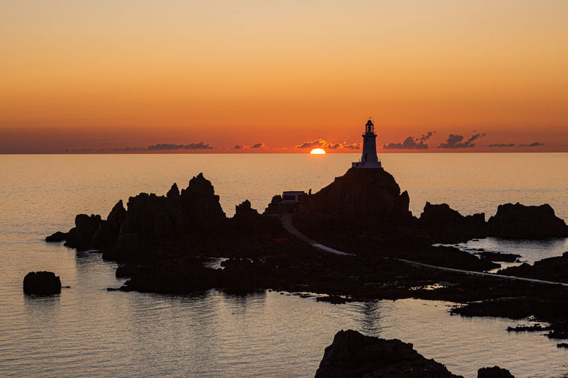 Silhouette rocks by sea against sky during sunset
